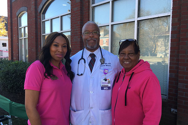 KAAAC staff standing with doctor at community mammogram screening.